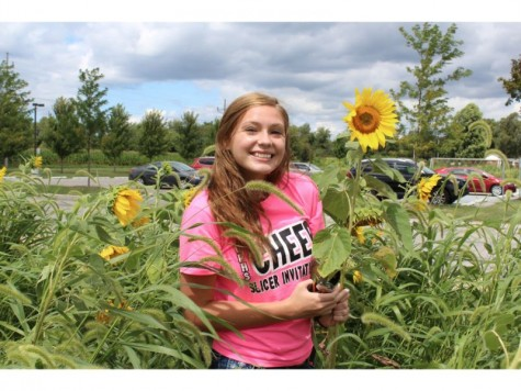 Photo by: Slicer Newsroom   Lexxie Glinos, junior, takes a minute to enjoy the sunflowers at Kesling Park.
